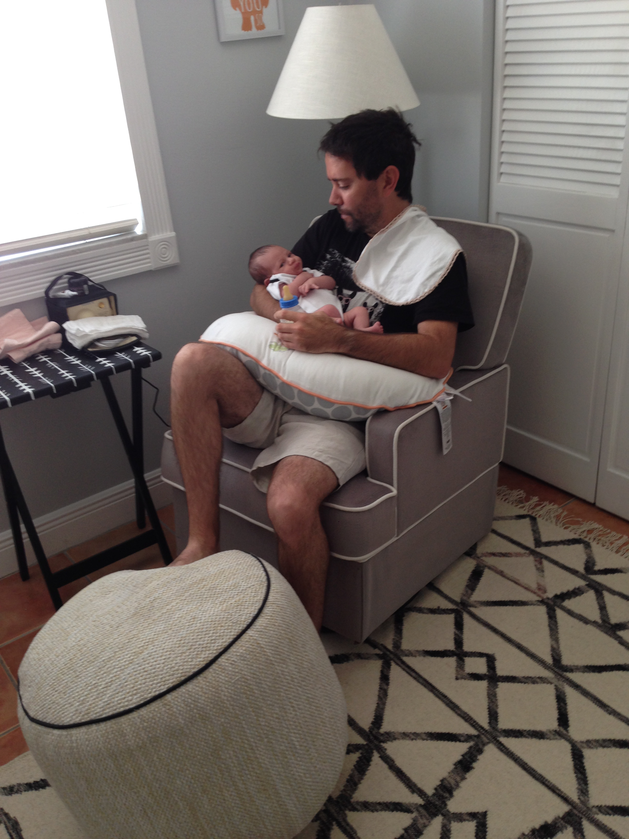 FF feeding Alfie on our glider. Ottoman from Target. Rug from West Elm. Folding table with Medela Breastpump.